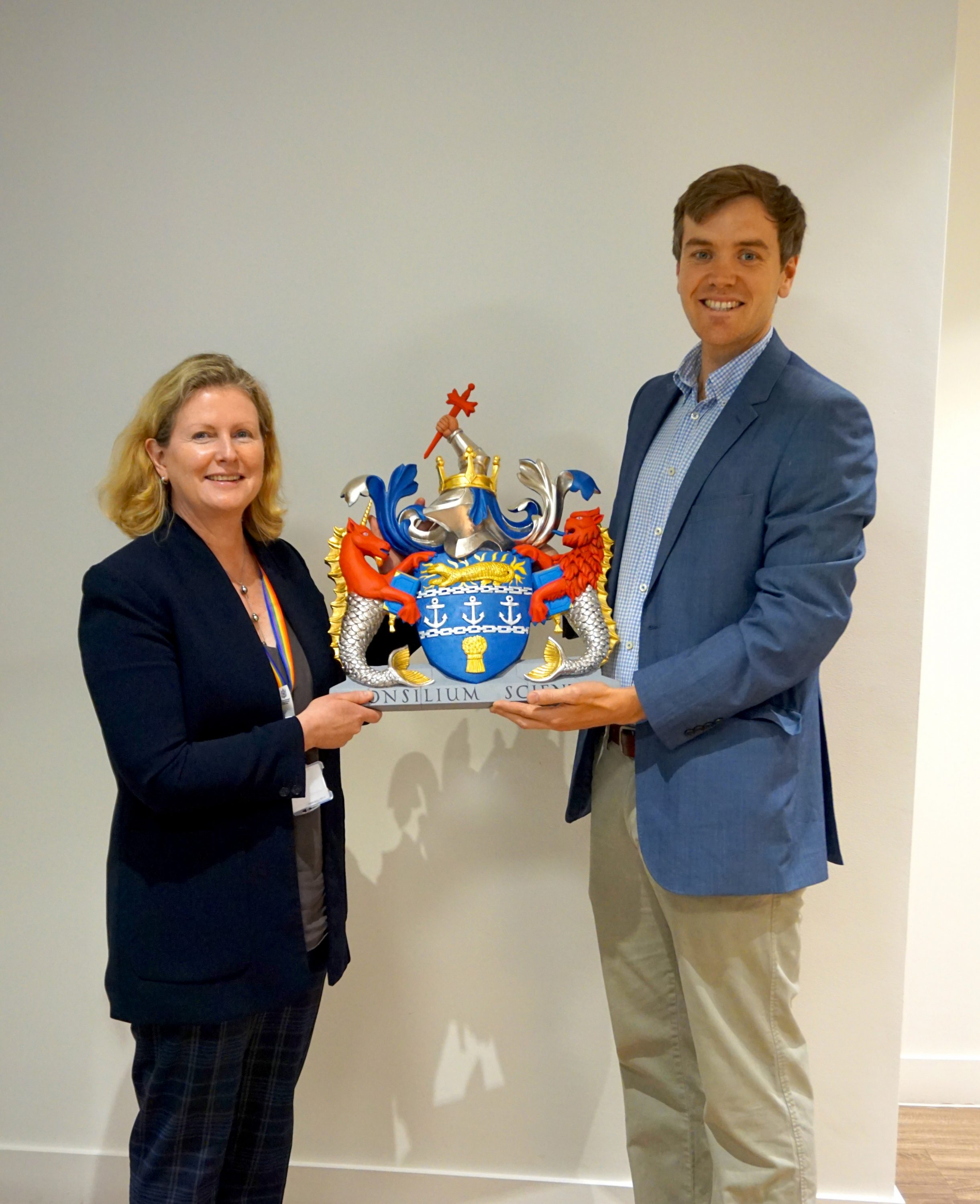 Sian Fisher CEO and William Barsley displaying the recently carved coats of arms